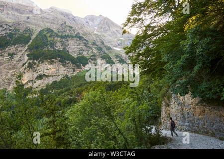 Female hiker in Pineta valley hiking trail at dusk in Ordesa y Monte Perdido National Park (Sobrarbe, Huesca, Pyrenees, Aragon, Spain) - Stock Image