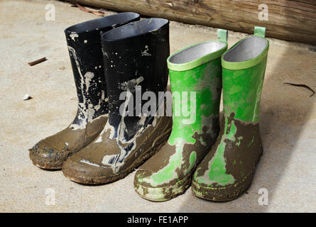 Children's muddy gumboots/galoshes drying in the sun. - Stock Image