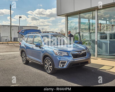 New blue 2019 Subaru Forester SUV at the dealership with a salesman and customer in Montgomery Alabama, USA. - Stock Image