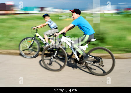 Russian kids on a summer day with bright sunshine rides their bikes in a typical village street in rural Russia - Stock Image