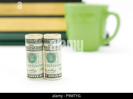 Focus on dollar currency highlights success built on knowledge and savvy advice seen in books in background - Stock Image