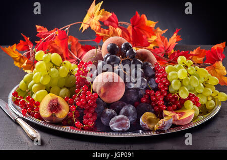 Autumn fruits in a tray on dark background - Stock Image