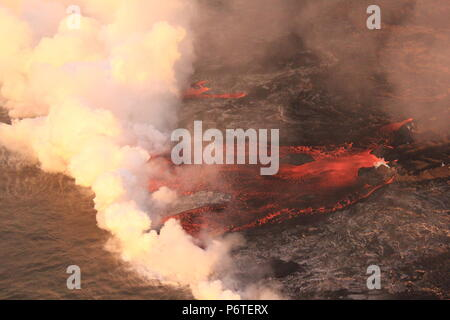 Lava from fissure 8 flows into the Pacific Ocean caused by the eruption of the Kilauea volcano June 30, 2018 in Hawaii. The recent eruption continues destroying homes, forcing evacuations and spewing lava and poison gas on the Big Island of Hawaii. - Stock Image