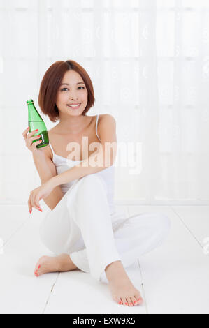 Young woman sitting and holding water bottle with smile, - Stock Image