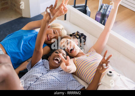 Portrait playful young women friends laying on bed - Stock Image