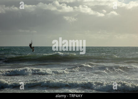Kite surfers surfing of the empty coast of Mullaloo beach,Western Australia achieving high speeds in windy weather conditions on a weekday afternoon. - Stock Image