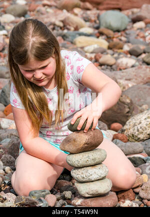Dunbar, East Lothian, Scotland, UK. 21st Apr 2019. European stone stacking championship: A child balances stones in the Quantity competition for children under 15 years of age –- most stones balanced vertically - at Eye Cave beach on the second day which comprises 2 competitions, a 3 hour artistic challenge and a children's competition. The overall winner receives a trip to llano Earth Art Festival & World Stone Balancing competition in Texas in 2020. Credit: Sally Anderson/Alamy Live News - Stock Image