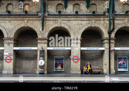 A lady sits alone, talking on her mobile phone, on a bench on a quiet platform at Notting Hill Gate London Underground Station. - Stock Image