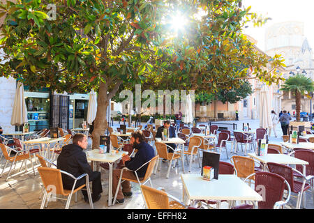 Customers in a street cafe in the Plaza de la Seu with sun glimpsing through trees - Stock Image