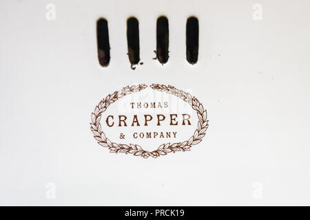 Logo on an old fashioned bathroom sink and taps made by Thomas Crapper and Company - Stock Image