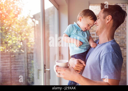Father holds toddler son while drinking coffee at home, by the window - Stock Image