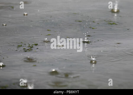 Heacham, Norfolk, England, UK. 27th July 2018. Heavy drops of rain break the dry spell falling into the sea at Heacham on the Norfolk coast. Credit: Stuart Aylmer/Alamy Live News - Stock Image