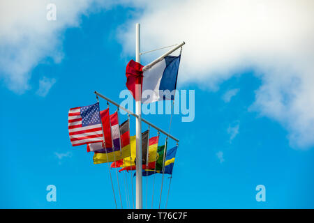 Flag pole in Gustavia, St Barts with numerous flags on display against a blue sky - Stock Image