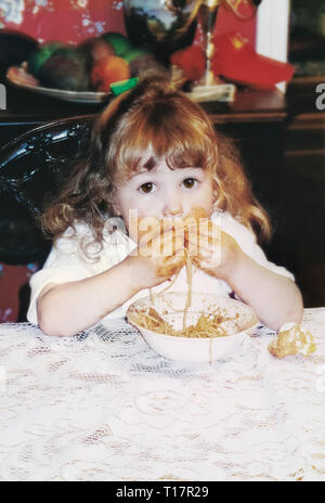Cute funny messy toddler girl age 2 with long curly blonde hair and big expressive brown eyes eating pasta and getting spaghetti all over her face - Stock Image