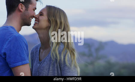 Low angle view of smiling couple touching noses in remote landscape - Stock Image
