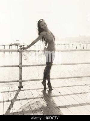 Woman in bathing suit on tiptoes posing on pier - Stock Image