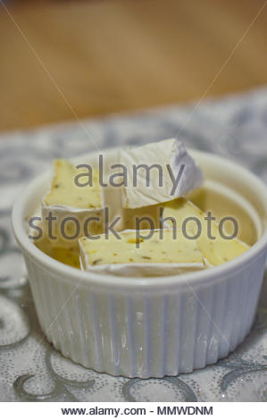 Fresh camembert cheese with herbs in a white bowl - Stock Image
