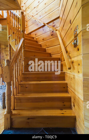 Pinewood staircase leading to upstairs floor from living room inside a piece sur piece Eastern white pine log and timber home - Stock Image