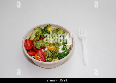 A white paper bowl with cooked and raw vegetables, garnished with feta cheese, on white background – vegetarian Mediterranean carry-out plate - Stock Image