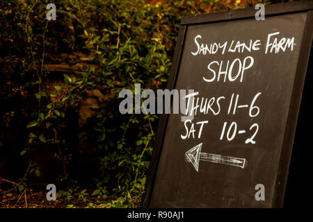 Close up of Sandy Lane farm shop blackboard with opening times. - Stock Image