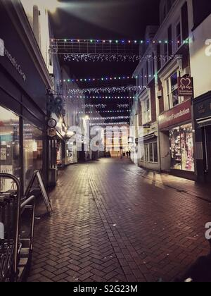 Empty British high street at night with Christmas lights - Stock Image