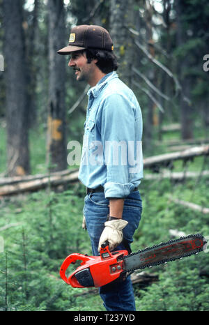 Young Man with Chain Saw Logging, MT, USA - Stock Image