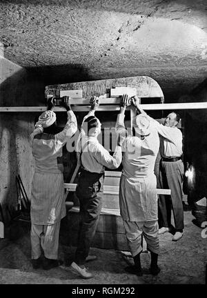 Howard Carter (second left) who discovered Tutankhamun's Tomb in the Valley of the Kings, Luxor, Egypt. November 1922 with two Egyptian workers and Arthur Callender working inside the tomb. Scanned from image material in the archives of Press Portrait Service - (formerly Press Portrait Bureau). - Stock Image