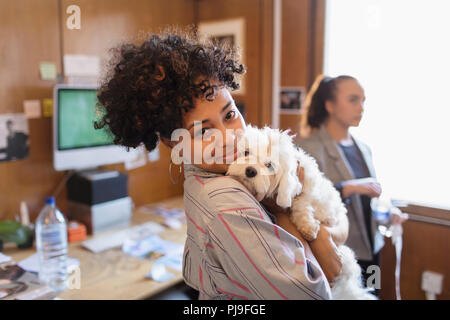Portrait smiling creative businesswoman with cute dog in office - Stock Image