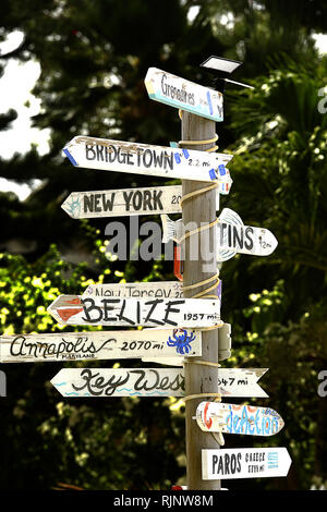 A home made dilapidated sign post visible along Coconut Beach, Barbados. The sign points to various locations and gives distances to each - Stock Image