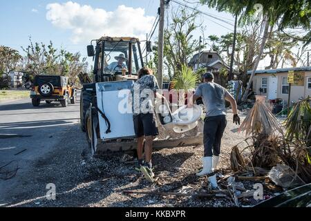 Residents and volunteers clear debris from their yards during relief efforts in the aftermath of Hurricane Irma - Stock Image