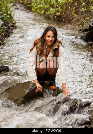 Woman kneeling in a creek. - Stock Image