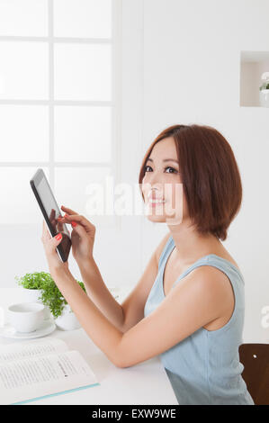 Young woman holding note pad and looking away with smile, - Stock Image