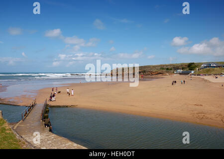 A footbridge across the River Neet or Strat at low tide looking across Summerleaze Beach in the Cornish town of - Stock Image