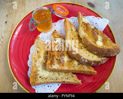 Buttered toasted multigrain brown bread and an open jar of marmalade, a  breakfast or afternoon tea snack in England UK - Stock Image