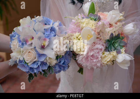 Caucasian women's hands holding two stylish bridal or bridesmaids bouquets - Stock Image