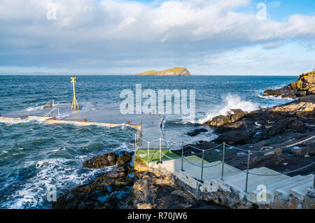 North Berwick, East Lothian, Scotland, United Kingdom. 7th December 2018. UK Weather: A bright sunny but very windy day in the seaside town with gusts of wind of up to 50-60mph forecast for today. Waves splash on the pier and rocks of the shoreline - Stock Image