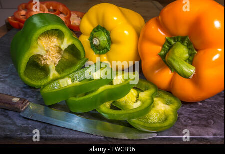 Food preparation: Three fresh uncooked peppers on a granite chopping board, one of them sliced, with a knife nearby. - Stock Image