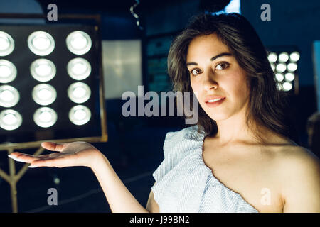 Portrait of attractive young sensual woman posing in studio against an illuminated background - Stock Image