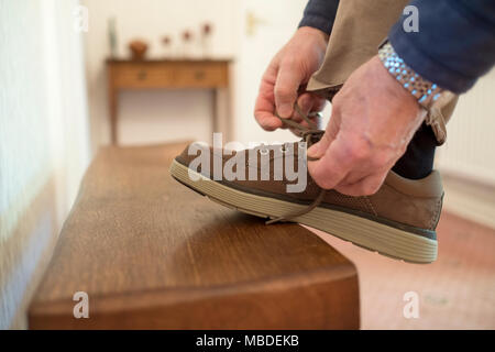 Man with foot on wooden bench tying shoe lace on brown suede shoe. - Stock Image