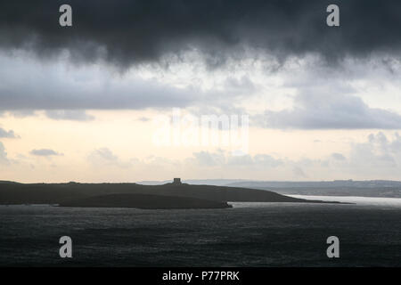 Dramatic weather with black clouds above a turreted shoreline as the ocean tide enters the river during the early evening, Devon, England. Europe. - Stock Image