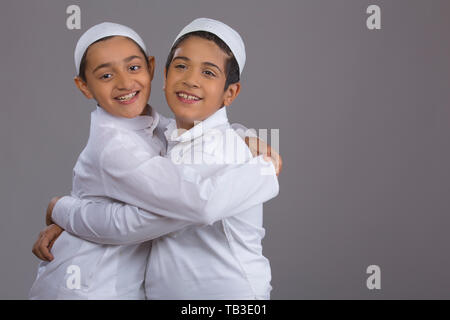 Young Muslim boys with caps side hugging each other - Stock Image