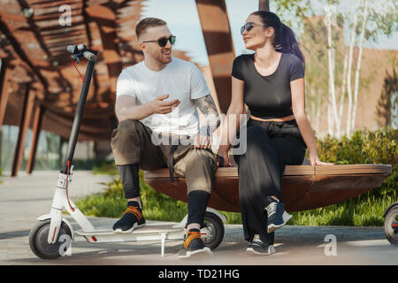 Couple of young man and woman sitting in park on wooden bench. - Stock Image