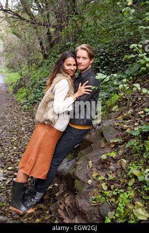 Woman leaning on man against a rock. - Stock Image