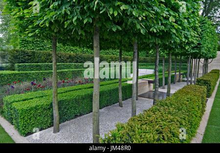 A classical garden with an avenue of yew, box and hornbeam leading to a water feature and sculpture - Stock Image