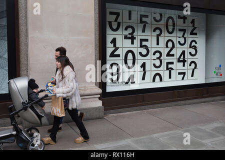 Parents walk past a window display that features numbers - part of a design theme called 'State of the Arts', at the Selfridges department store on Oxford Street, on 4th March 2019, in London England. Darren Almond's piece 'Chance Encounter 004', consists of a grid formed from rectangular panels, featuring fragmented numbers that appear to scroll across the surface.  State of the Arts is a gallery of works by nine crtically-acclaimed artists in Selfridges windows to celebrate the power of public art. - Stock Image