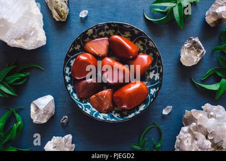 Red Jasper and Quartz on Blue Table - Stock Image