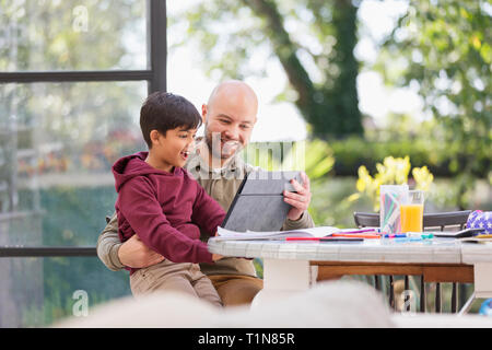 Father and son using digital tablet at table - Stock Image
