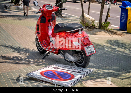 Illegal parking. Motorbike parked on the pavement having also demolished the no parking sign. Thailand, Southeast Asia - Stock Image
