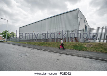 Anonymous grey industrial shed, empty road, grey sky and woman pedestrian carrying shopping along pavement.  Willenhall, West Midlands, UK, July 2014 - Stock Image