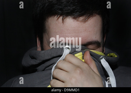 man hiding face with grey hoodie - Stock Image